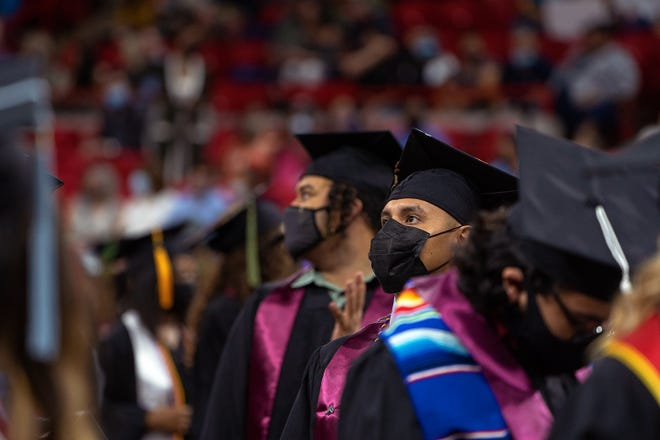 MSU students looks into the crowd as people find their seats during the processional at Saturday's commencement ceremony.