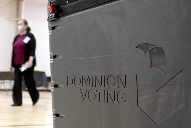 A worker passes a Dominion Voting ballot scanner while setting up a polling location at an elementary school in Gwinnett County, Ga., on Jan. 4, 2021. [AP PHOTO/BEN GRAY]