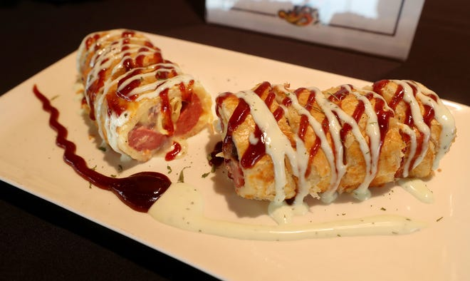 The Dog Check Roll is a footlong, all-beef hot dog stuffed with a mix of Stouffer's White Cheddar Mac & Cheese and pulled pork, wrapped in a puff pastry, baked and cut into small pieces like a sushi roll and drizzled with BBQ sauce and Cusabi sauce. Unlike a typical ballpark hot dog, this version is served with chopsticks.