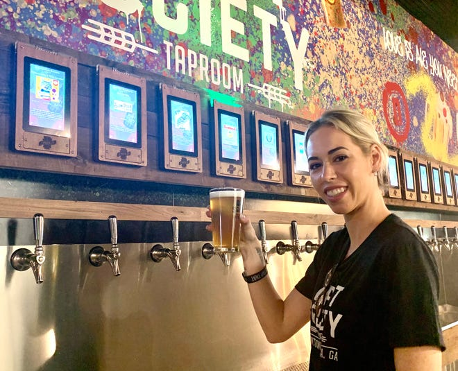 Draft Society Taproom general manager Ashley Valdes toasts with a pint of Watermelon Gose from Terrapin Beer Co. that she pulled from the self-serve tap machine.