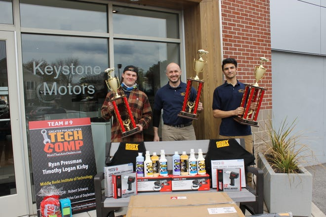 Middle Bucks Institute of Technology seniors Logan Kirby (left) and Ryan Pressman (right) pose with teacher Robert Schwarz in front of Keystone Volvo of Doylestown. The students recently took first place in the 2021 Greater Philadelphia Auto Technology Competition.