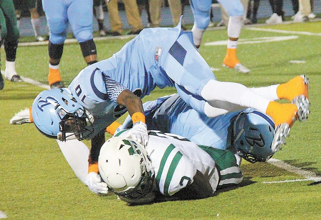 Bartlesville Bruin great A.J. Parker helps bury the Muskoee quarterback in a sea of blue during the 2015 campaign.