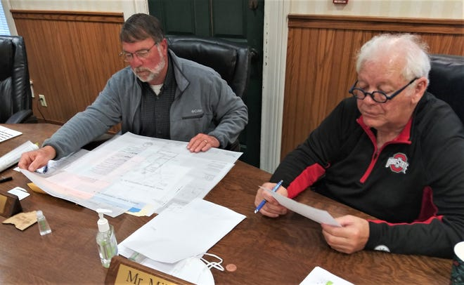 Rob Ault, left, the chairman of the Holmes County Board of Commissioners, looks over a plat for a project in Paint Township, as Commissioner Joe Miller looks over other documentation during Monday's meeting.