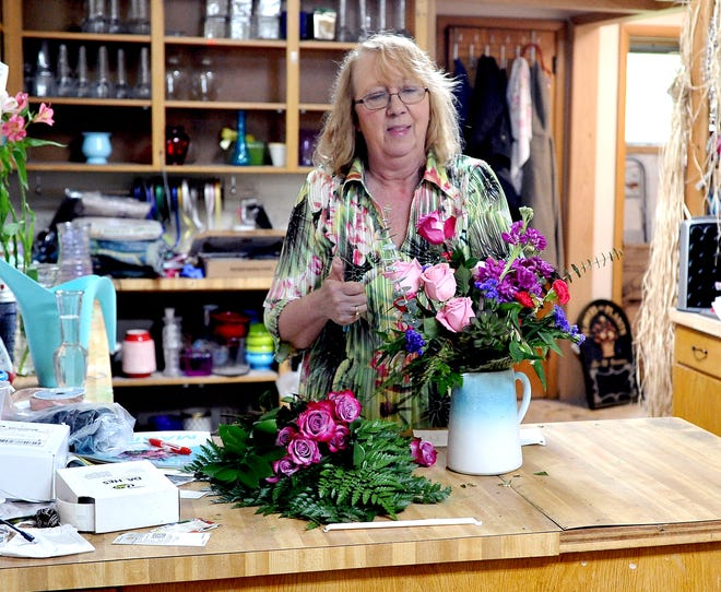Claudia Grimes, the owner of Green Thumb Floral, works on a colorful arrangement in her shop on the south end of Wooster near the Ohio State University campus.
