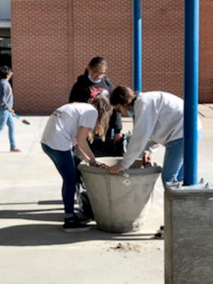 DCMS student council students plant new flowers around the DCMS campus during Campus Cleanup Day held on April 29.
