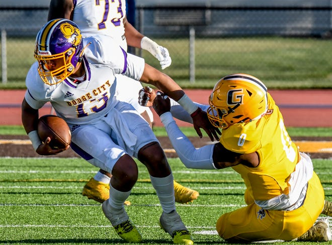 Dodge City Community College quarterback Rashad McKee, left, avoids an attempted sack by Garden City's Raymond Cutts to keep a play alive Saturday at Broncbuster Stadium in Garden City. The Conquistadors fell in the rivalry game to the Broncbusters, 34-24.
