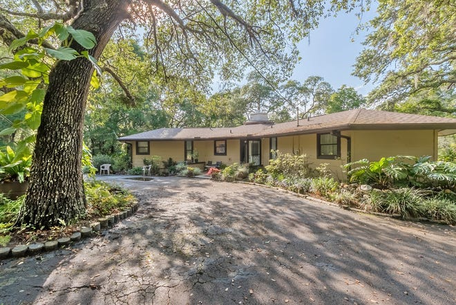 This truly unique Pierson property, nestled on nearly three acres  on a spring-fed lake, has a two-bedroom, two-bath main home, with a dedicated office, a separate guesthouse and a 945-square-foot detached concrete-block garage/workshop, with a full bath.