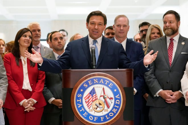 Surrounded by lawmakers, Florida Gov.Ron DeSantis speaks at the end of a legislative session, Friday, April 30, 2021, at the Capitol in Tallahassee.