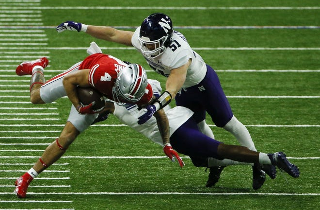 Ohio State Buckeyes wide receiver Julian Fleming (4) is tackled by Northwestern Wildcats linebacker Blake Gallagher (51) and Northwestern Wildcats defensive back A.J. Hampton (11) during the first quarter of the Big Ten Championship football game between the Ohio State Buckeyes and the Northwestern Wildcats on Saturday, Dec. 19, 2020 at Lucas Oil Stadium in Indianapolis.