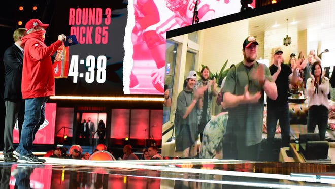 An image of Oklahoma center Creed Humphrey is displayed on a screen, right, after a second-round pick by the Kansas City Chiefs at the NFL football draft Friday in Cleveland.