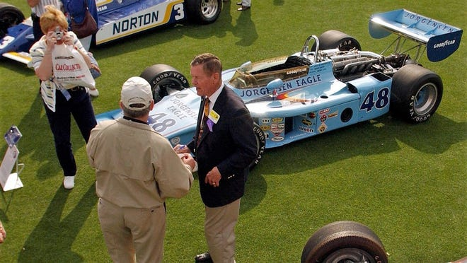 Legendary race car driver Bobby Unser (center in sport coat) signed autographs and posed for photographs surrounded by several of his former Indy Race Cars as part of the ninth annual Amelia Island Concours d'Elegance. Unser passed away on May 2 at age 87.