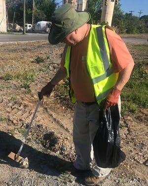 Harvey Hamrick picks up a piece of wood on Market Street during the litter sweep.
