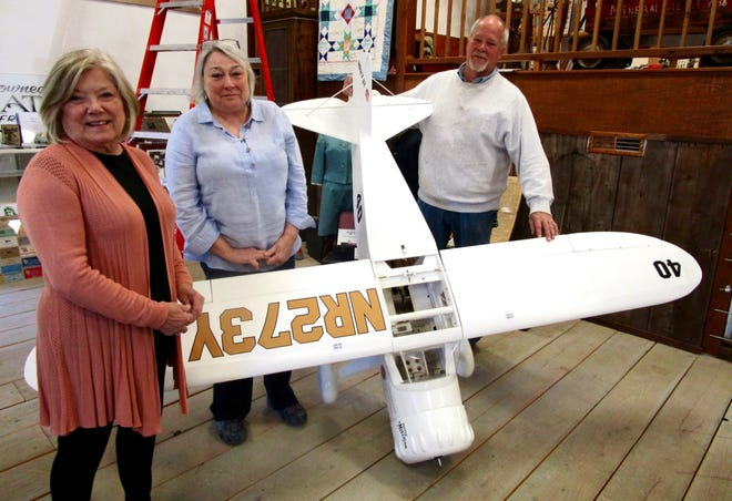 """Angie Snook, left, retired curator of the Geneseo Historical Museum; Paula (Neumann) Chapa, chairman of the Harold Neumann Project; and Bob Johnson, pilot, are shown by the miniature replica of Neumann's """"Mr. Mulligan,"""" which is included in the """"Harold Neumann –Aviation Pioneer"""" exhibit at the museum."""