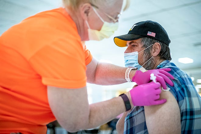 Todd Caulkins of Peoria receives an injection from Terena Gyovai RN at the Knox County Unified Command Vaccine Center walk-in clinic in the former Bergner's store on Saturday, May 1, 2021.