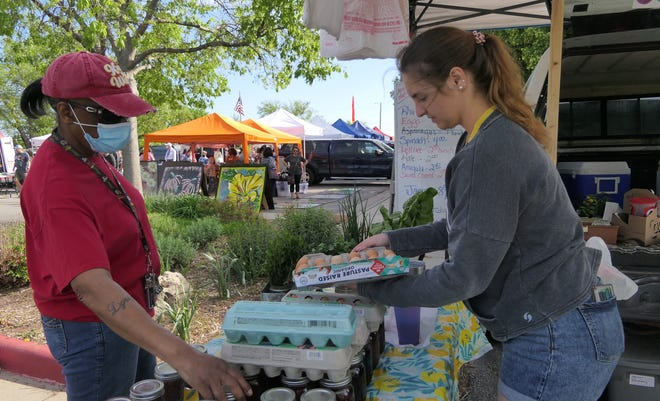 Pat Redmond of Wichita buys home-grown, pasture-raised eggs and jelly from Gianna Leland of Pretty Prairie at the Kansas Grown! Farmers Market in Wichita.