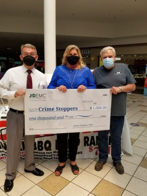 Crime Stoppers Chairman Donnie Worrell (left) accepting a donation from Jones/Onslow Electric Membership Corporation at the program's annual fundraiser on Friday.