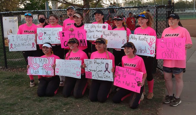The Newton High School softball team wore pink jerseys Friday for cancer awareness. The team showed off signs of who they were playing for Friday.