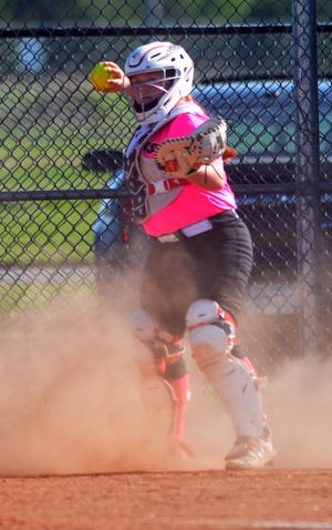 Newton catcher McKenzie Cusick makes a throw during play Friday against Campus. Newton split with the Colts.