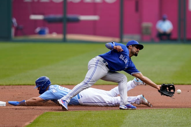 Kansas City Royals Whit Merrifield, left, steals a base behind Toronto Blue Jays second baseman Marcus Semien, right, during the first inning of a baseball game at Kauffman Stadium in Kansas City, Mo., Sunday, April 18, 2021.