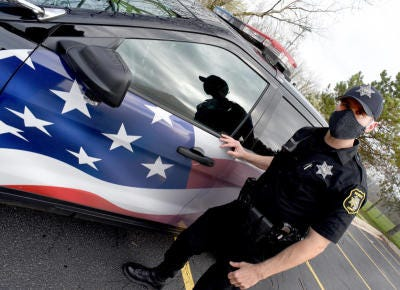 Monroe County sheriff's Deputy Brian Sroka stands next to his patrol vehicle decorated with an American flag.