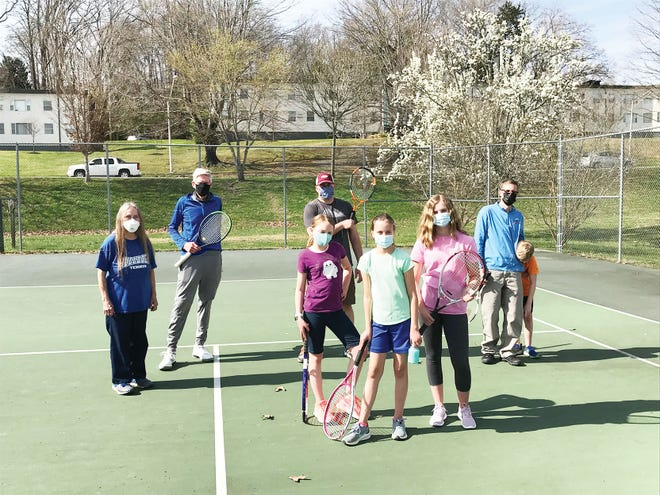 Junior players currently in grades 6 through 11 are invited to play recreational summer tennis. Pre summer play will be held from 4 to 5 p.m. Friday afternoons through May, at the Jackson Square tennis courts. Summer days and times TBA.   Masking will be required. Contact AnnFrome@gmail.com for additional information. Pictured are facilitators Ann Frome and Dennis Strickler, left, with the spring break players and their Dads, right. Special to The Oak Ridger