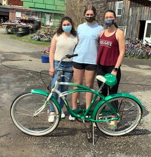 """Members of Colgate University's Tri Delta sorority volunteered April 24 to clean bikes at Community Bikes in Hamilton as part of the organization's community philanthropy program. Serelle Carr, left, Emma Peck, center, and Catie Morgan pitched in to spend an afternoon helping out as Community Bikes prepares for two Bike Days this spring, where bikes will be distributed to low income families in Madison County. """"It was great of the students to make time to help,"""" said Community Bikes' Chuck Fox. """"Colgate students have always been generous in volunteering and this year their help is especially appreciated."""""""