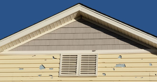 Holes in home siding from damage by hail storm.