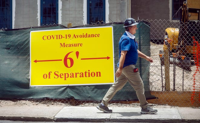 A worker walks past bright yellow social distancing sign in front of construction site at the intersection of South Ocean Boulevard and Hammon Avenue in this May 2020 photo.