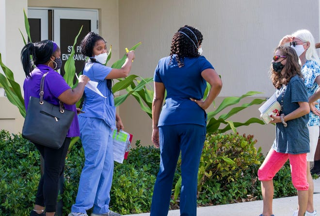 A healthcare worker checks in people for their COVID-19 vaccinations at the Greenacres Community Center Thursday morning, April 29, 2021. The City of Greenacres and the Florida Department of Health hosted the appointment only event, which offered 450 Moderna doses.