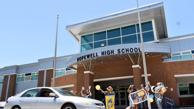 In this spring 2020 file photo, Hopewell High School teachers cheer as graduating seniors pass by the school in their cars. The pandemic delayed Hopewell's plan to launch its balanced-calendar schedule, so now the city  will introduce year-round schooling this July.