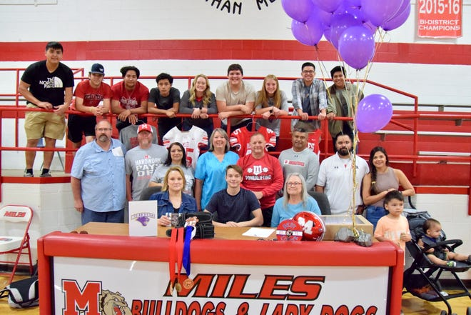Friends and family gather around as Radek Spatz (center, blue shirt) signs his National Letter of Intent to attend McKendree University on a powerlifting scholarship.