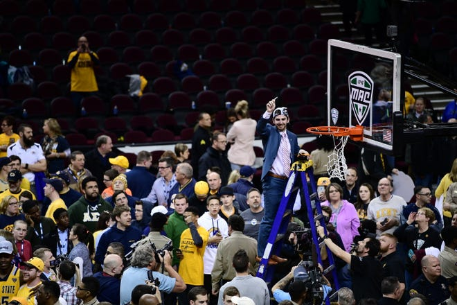 Assistant coach Brian Barnes displays his piece of the net after the Kent State men's basketball team captured the 2017 MAC Tournament championship in Cleveland.