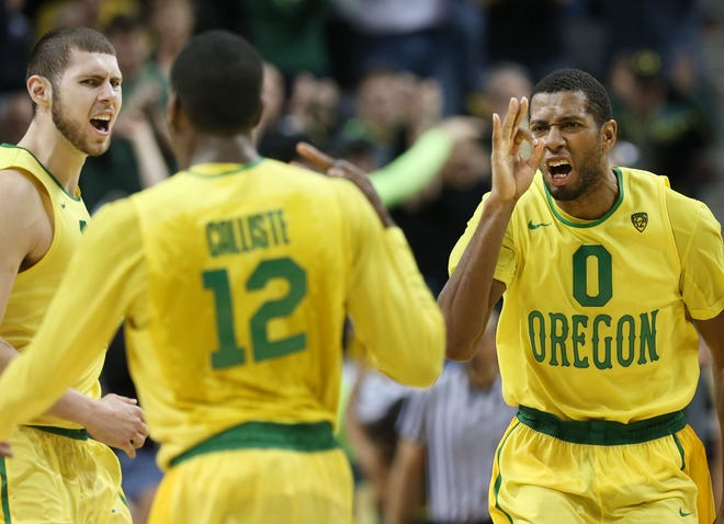 Mike Moser, right, celebrates with teammates Ben Carter, left, and  Jason Calliste, center, during a game against Arizona in Eugene, Ore. on Saturday, March 8, 2014.