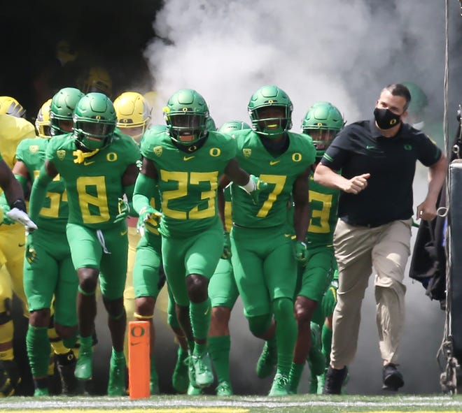 Oregon coach Mario Cristobal, right, will be looking to lead the Ducks to their third straight Pac-12 championship.