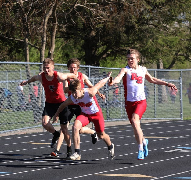 Roland-Story's Eli Thorson hands the baton off to Nate Johnson during the sprint medley relay at the Norsemen Relays April 29 in Story City. Roland-Story won the event on its way to placing first in the team standings.