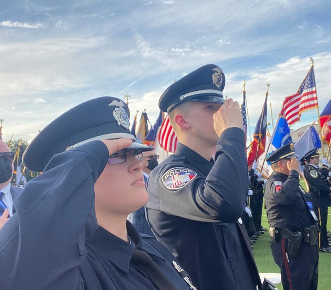 Officers Maureena Salazar and Hayden Bridges salute during the Texas Peace Officers' Memorial and Candlelight Vigil in Austin on Sunday.