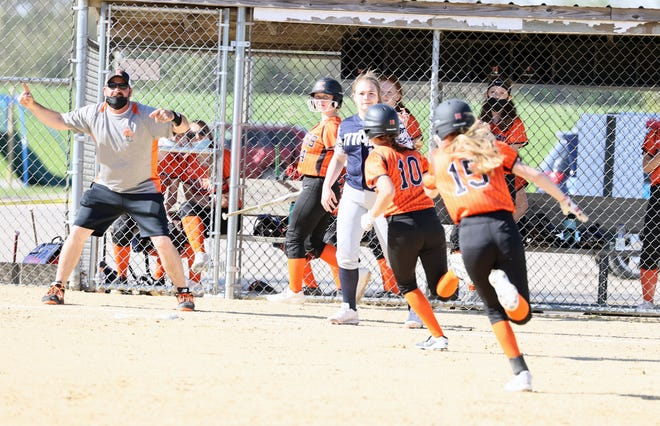 Assistant coach J.R. Salisbury waves home Kendal Bennison and his daughter, Makaela Salisbury, on an inside-the-park home run in a Friday victory over Monmouth-Roseville at Northeast Park.