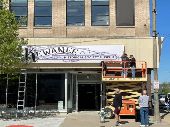 """Dennie Packee, right, and Dennis Cleaver, of Reiman's Harley Davidson, install the sign on the front of the Kewanee Historical Society's new museum at 125 N. Tremont St., Friday, putting the """"finishing touch"""" in place before the museum opened for the season Saturday afternoon. Photo by LeeAnn Baillieu"""