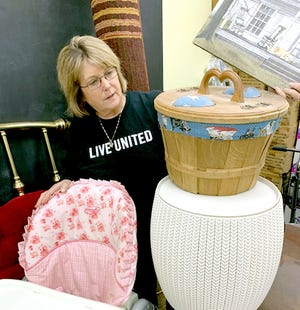 """Kelly Hostetler, executive director of St. Joseph County United Way, shows off some of the items the agency will include at its community garage sale this weekend. """"Yards, Barns and Brews"""" takes place May 7-8 at the St. Joseph County fairgrounds."""