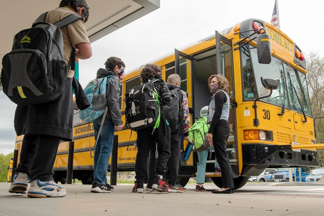 Students are dismissed to their bus at the end of the first day of full-time in-person classes at Nelson Place Elementary School in Worcester Monday.