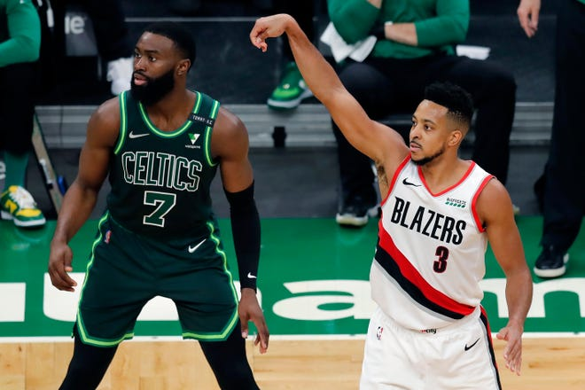 Portland's CJ McCollum shoots a 3-pointer against Boston's Jaylen Brown during the second half of Sunday's game.