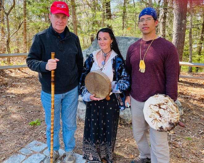 Bob Kelley, Mary Michael, and Marcus Hendricks stand before the hand-chiseled Cairn, which recognizes the last resting place of the Indigenous Peoples of Yarmouth.