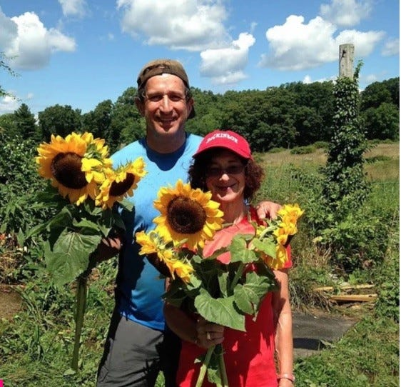 Rona and Tim Carroll holding sunflowers on the farm.