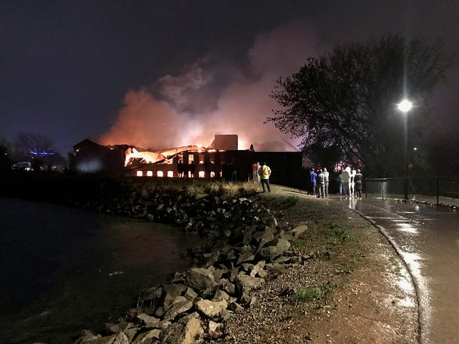 Onlookers watch a fire burn Sunday at the Whiting Mill in Menasha.