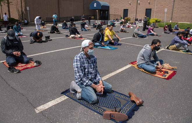 Due to COVID-19 capacity restrictions, some members of the Muslim community worship in the parking lot of the Gracious Center of Learning and Enrichment Activities in Cherry Hill, while others worhsip inside the building, during a prayer service on Friday, April 30, 2021.