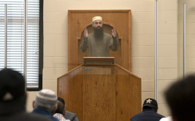 Imam John Starling stands behind plexiglass as he leads a prayer service in the Gracious Center of Learning and Enrichment Activities in Cherry Hill on Friday, April 30, 2021.