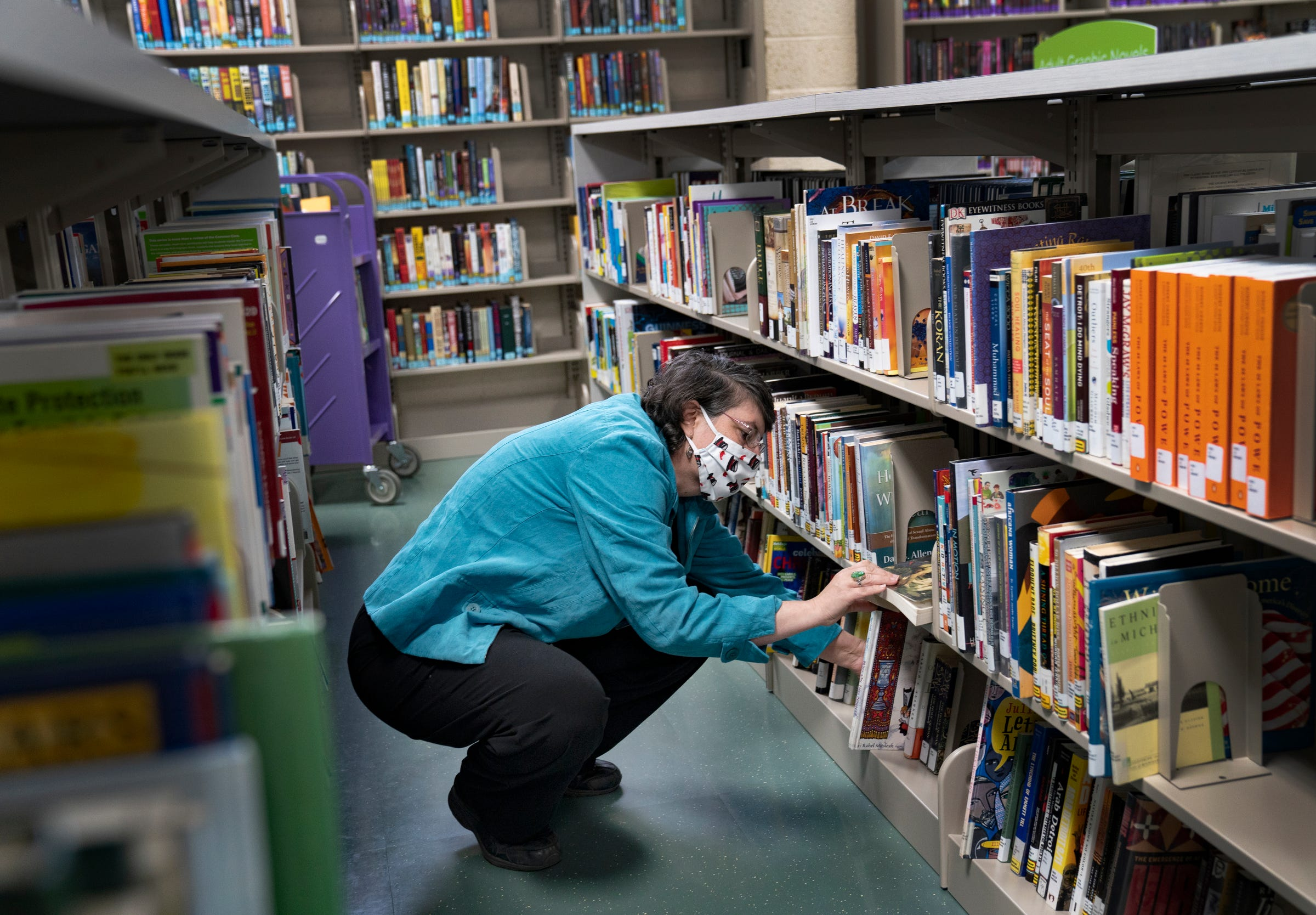 Mary Jo Vortkamp, 52 of New Haven, reshelves books on Thursday, April 29, 2021 at the Detroit Public Library Jefferson Branch. Vortkamp is the manager and children's librarian at the Jefferson Branch. Vortkamp was formerly at the Franklin Branch that closed in March 2020.