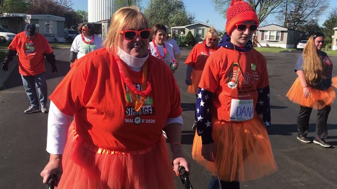 Dana Roca of Fremont, pictured center, walks with Luke Casselman and other friends and family Saturday at Roca's virtual multiple sclerosis (MS) walk in her neighborhood. Roca was diagnosed with MS in 2009 and used Saturday's event to raise awareness and money MS research.