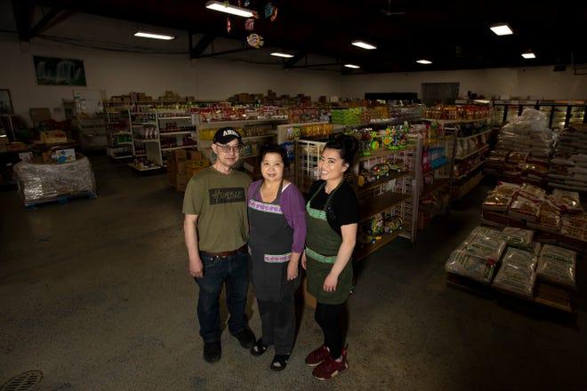 Bruce Yang, Kao Shoua Yang and their daughter Tara in their shop, Main Oriental Market, 607 Main St., Green Bay.