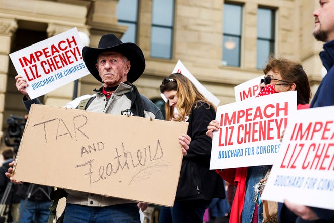 """A man carries a """"Tar and Feathers"""" sign before Rep. Matt Gaetz, R-Fla., speaks at a rally against Rep. Liz Cheney, R-Wy., on Jan. 28, 2021 in Cheyenne, Wyo. Gaetz added his voice to a growing effort to vote Cheney out of office after she voted in favor of impeaching Donald Trump."""